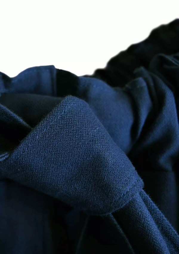 Detail of oversized dark blue trousers made from sustainable cotton