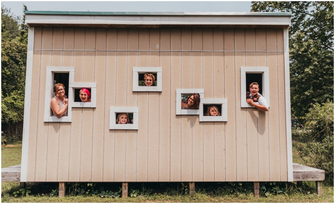 Newly weds with friends posing out of little windows in the side of a small building. | My Eastern Shore Wedding |