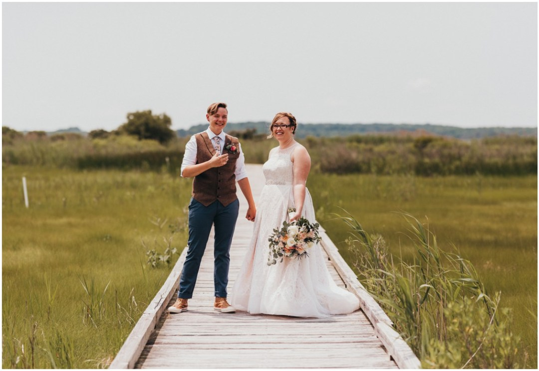 Married couple on long dock in the middle of tall grasses. | My Eastern Shore Wedding |