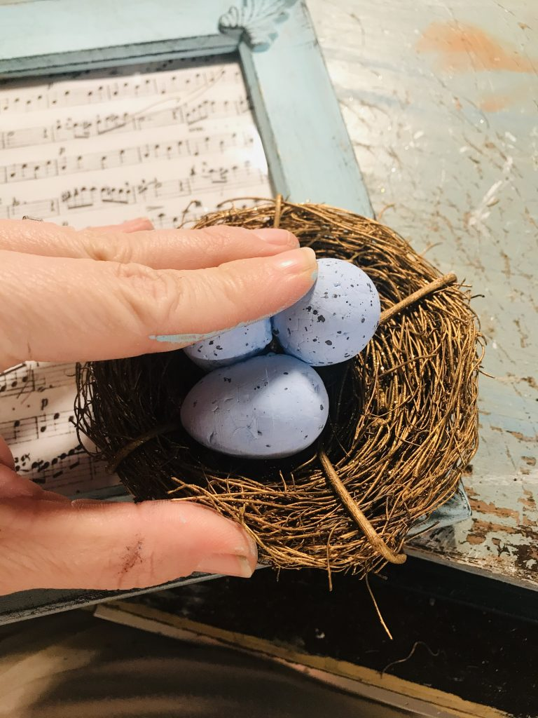 attaching a birds next filled with eggs to a painted blue frame with sheet music inside