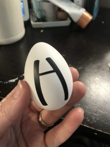 vinyl letter being added to a white easter egg