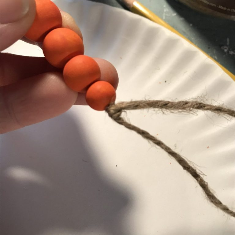 tying off the twine at the bottom of a wood bead carrot
