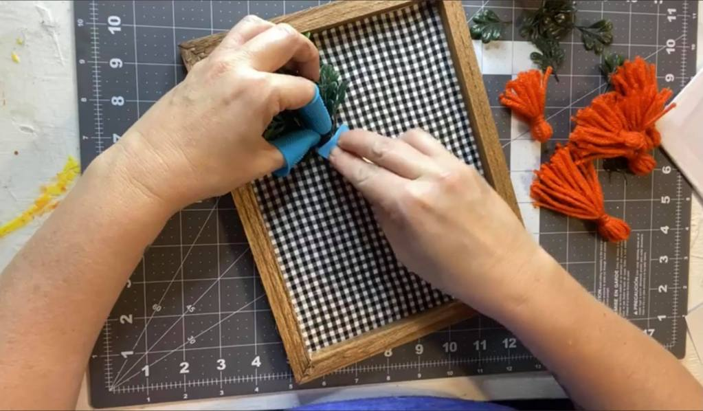 adding greenery for a carrot onto a black gingham framed canvas