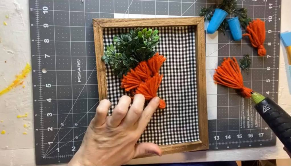 adding orange tassels to a gingham background to make a carrot