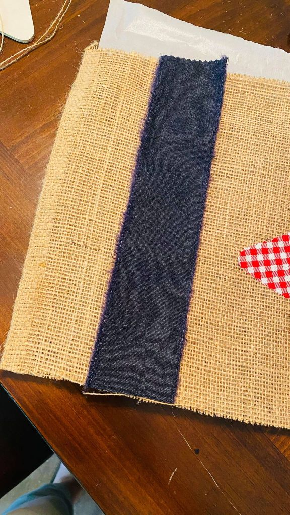 adding blue jean ribbon to the edge of a burlap table runner