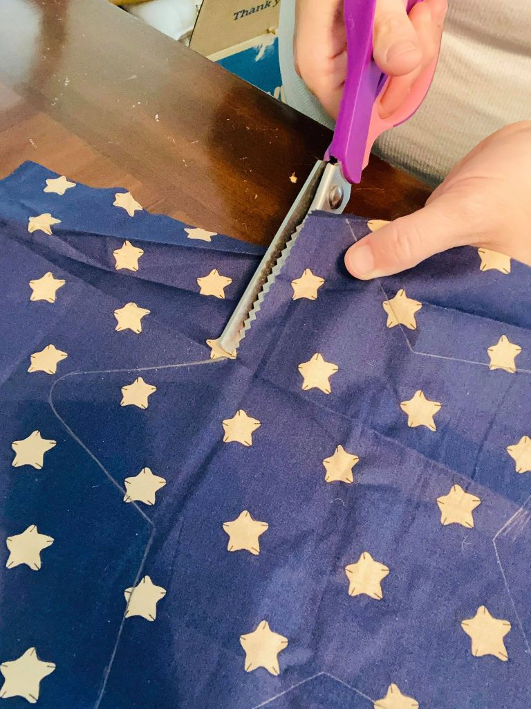 cutting stars out of fabric for a patriotic table runner #patriotictablerunner