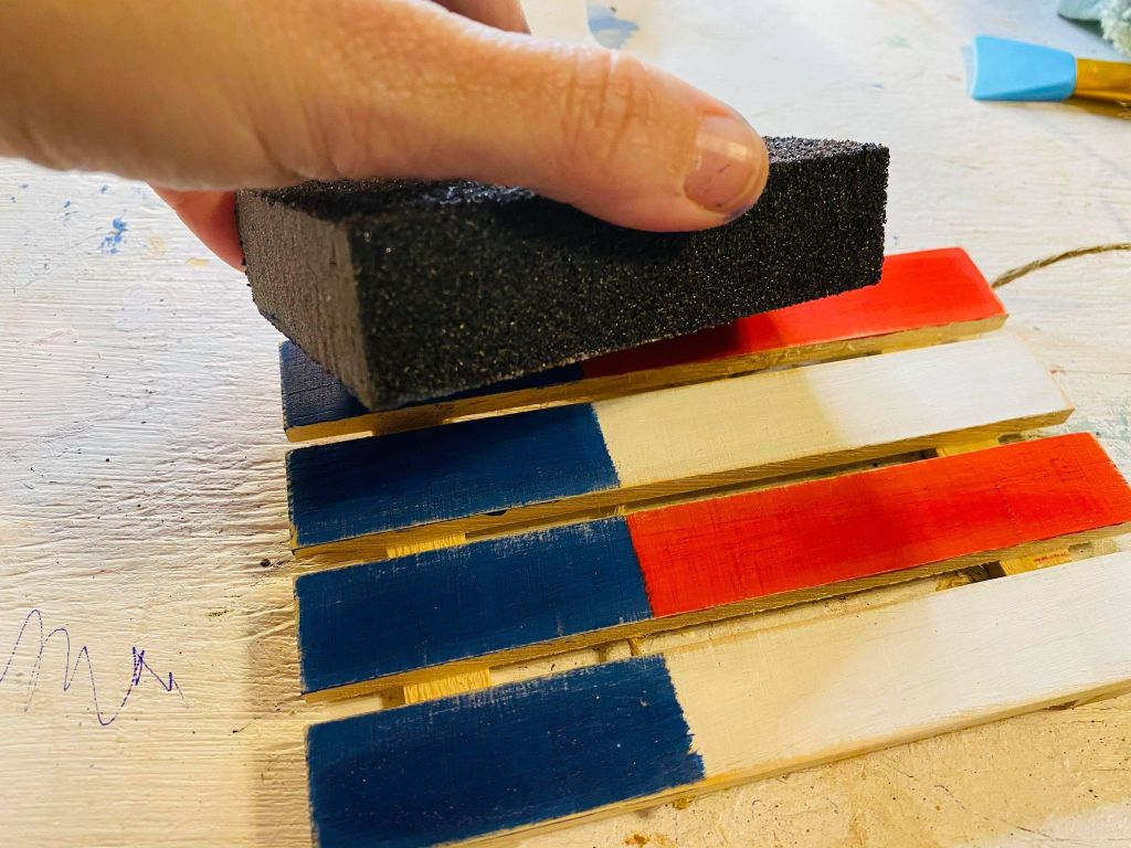sanding a mini pallet painted red white and blue
