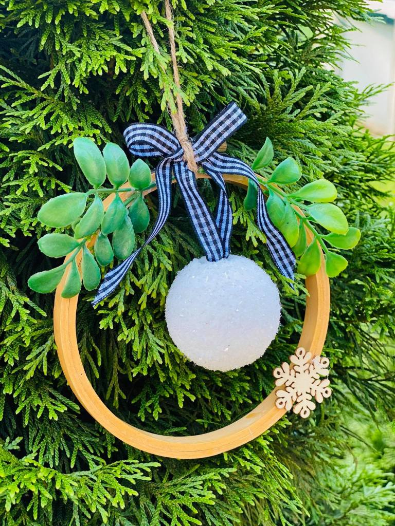 styrofoam ball covered in diamond dust hanging from a ribbon hanger in the center of an embroidery hoop #styrofoamcrafts #styrofoamchristmasornament