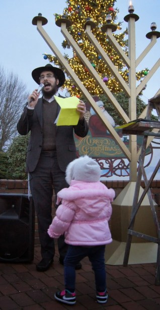 The rabbi speaks as his daughter watches.