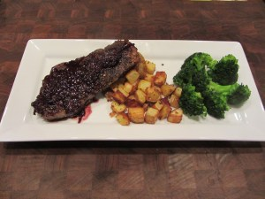 After the steak has rested for 10 to 15 minutes start plating! The potatoes should be nice and crispy, and whatever vegetable you decide to prepare should be done as well. I steamed a head of broccoli to go with our dinner. After plating, drizzle the red wine reduction sauce over the steak and onto the potatoes if you like.