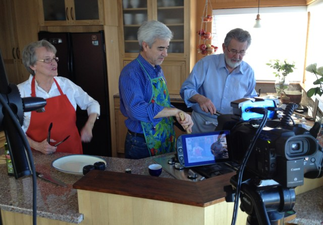 "Michael Miropolsky, center, conductor of Edmonds' Cascade Symphony Orchestra, joined Konkydoodle Kitchen's Carol Kinney and Doug Lofstrom Friday to videotape two segments for Konkydoodle's popular YouTube cooking show. Michael prepared two of his favorite recipes from the symphony's cookbook ""Measures and Pleasures."" The videos will appear soon on MyEdmondsNews.com and on other popular websites. (Photo by Chuck Woodbury)"