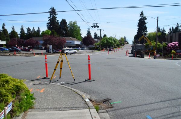 Barricades are already in place and crews are busy at Five Corners as construction of the new roundabout begins.  The overhead lines in this photo will soon be a thing of the past; part of the roundabout design calls for undergrounding power and other utilities.