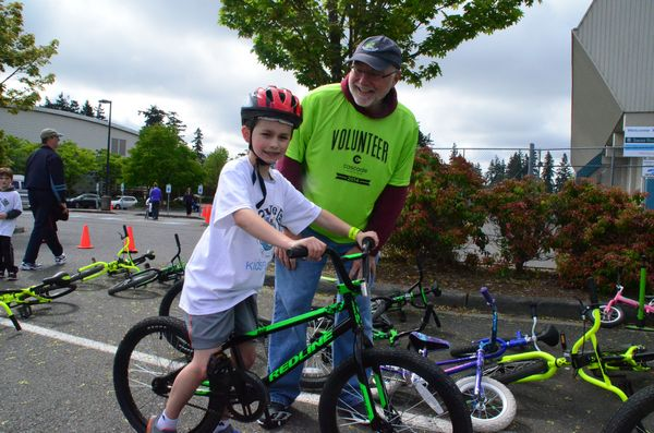 Cascade Bicycle Club's John Larpenter helps Tyler Shankle get set up to go through the bicycle rodeo course.