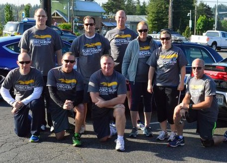 The combined team from the Edmonds and Mountlake Terrace Police Departments met at 212th and Highway 99 to await the pass-off of the Special Olympics torch from the Lynnwood PD runners. L to R kneeling: Josh McClure (Edmonds), Jason Robinson (Edmonds), Mark Marsh (Edmonds), Kevin Pickard (MLT).  L to R standing: Dennis Smith (Edmonds), Ken Crystal (Edmonds), Brad Halston (Edmonds), Heidi Froisland (MLT), Becky Hill (MLT).