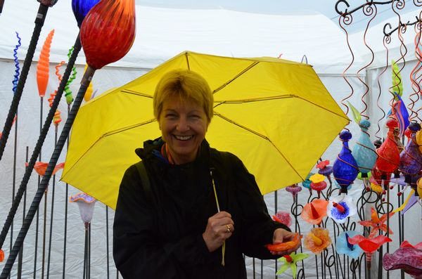 "Bellevue resident Sue Gilbert brings a splash of color with her yellow umbrella. ""I never miss the Edmonds Arts Fair,"" she said. ""Rain or shine, it's a must-see event for me."""