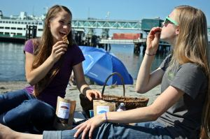 Emma and Keturah enjoy a Rain City Crunch snack on  a sunny Edmonds day.