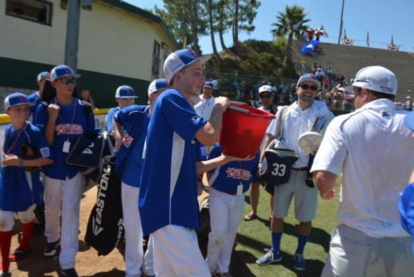 arsen Tjarneberg (left) gets ready to douse Pacific Little League manager Robley Corsi II with some water.