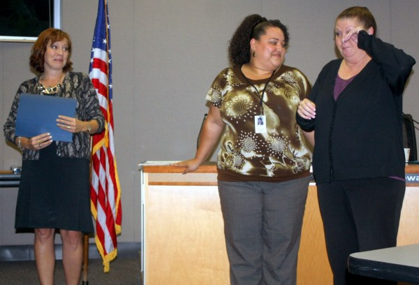 Edmonds School District employee LeAnne Brisbois (right) brushes away a tear during a presentation honoring her efforts to feed homeless students in the Edmonds School District. Board President Diana White (left) and District Diversity, Equity and Outreach coordinator Karena Hooks both praised Brisbois' work and dedication to helping students.