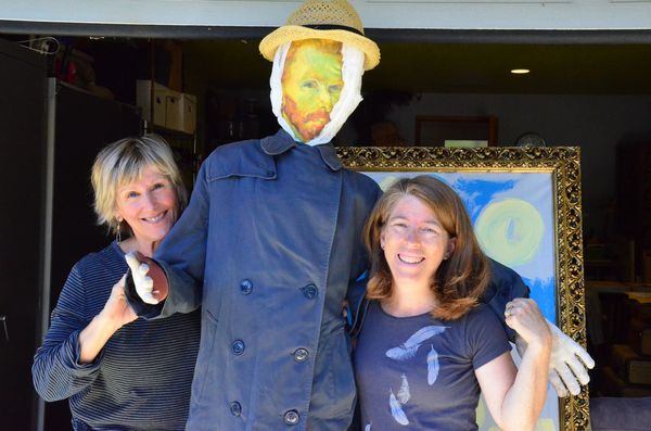 """Vincent van Go-Crow, flanked here by creators Mona Smiley-Fairbanks (R) and Robin Westbrook (L), is the first entry in this year's Edmonds Scarecrow Festival to hit the streets. Go-Crow is now displayed on """"the fence,"""" an outdoor display area adjacent to the ArtWorks at Second in Dayton in downtown Edmonds."""