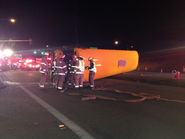 Shorelines Firefighters stand by the overturned bus with shattered glass from the windshield at their feet.