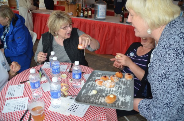 Tasteoff coordinator Theresa Poalucci right, serves Hawaiian doughnuts -- another judges' favorite -- to Cheryl Reagan.