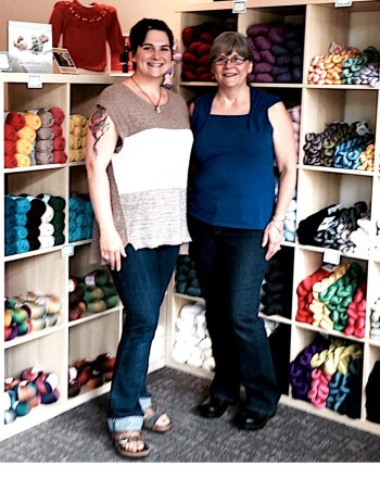 Nona and Leslie pose in front of their colorful yarn inventory at All Wound Up in Perinville.