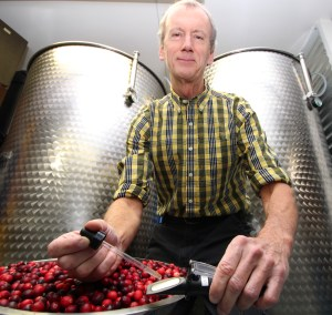 Core Hero founder Steve Kaiser applies a few drops of cranberry juice on a refractometer to measure the Brix or sugar level.