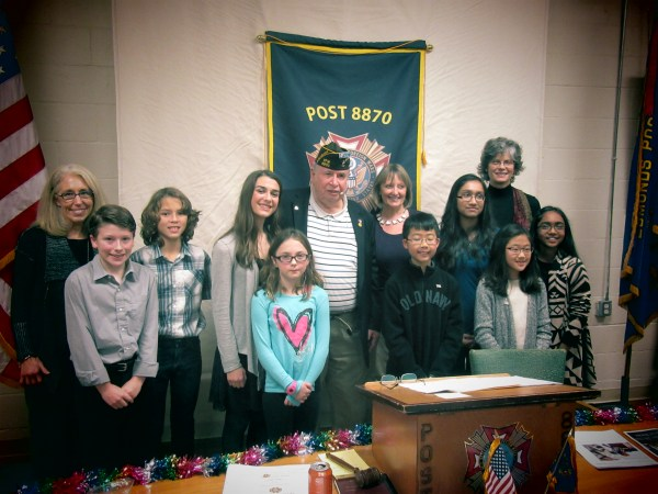 Post Commander Jim Blossey joins student essay winners and their teachers.  L-R Front Row: Eli Faris, Sabrina Windland, Benjamin Hoang, Chloe Lee, and Mohuwa Wahid.  Back Row: Lori Kutrich, Deacon Fuentes, Olivia Olson, Jim Blossey, Aina Green, Lara Wahid, and Sue Idso.