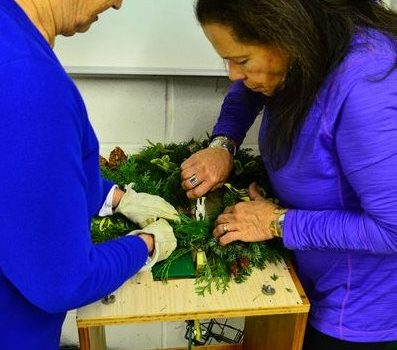 Cindy Norman and Janice Noe attach a variety of fresh-cut floral material to a wreath frame.