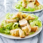 two plates of caesar panzanella salad