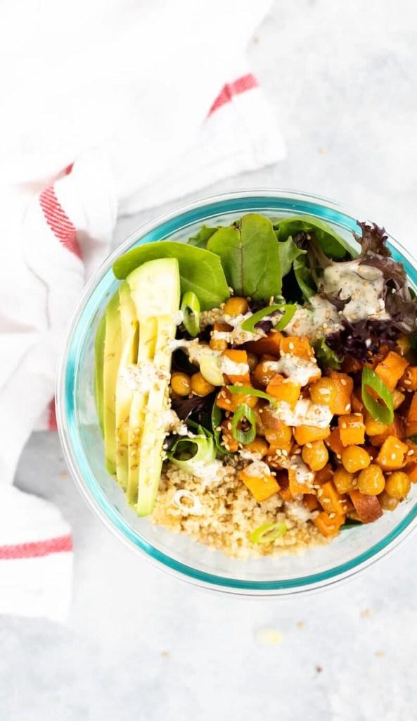vegan meal prep bowl with quinoa, greens, and avocado