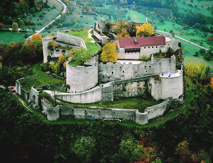 An aerial view of Neuffen Castle (Acknowledgement: image from Wikimedia – (Swabian Tourismusverband). When coming to the castle, the tunnel exit is on the left side of the image. Then the road passage goes uphill steeply (from left to right of the castle). This then leads to the entrance to the castle proper.