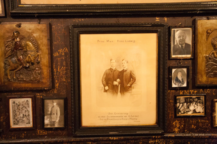 The restaurant walls, dining tables and chairs are covered with graffiti and engravings. It has become a trademark of this restaurant. On the Walls are photographs of well known personalities – Prinz Max and Prinz Ludwig in this case.
