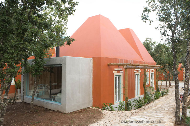 """The reception-lounge building known as the """"Mother House"""" of Luz Houses is built in a traditional Central Portugal style with its pyramid roof."""