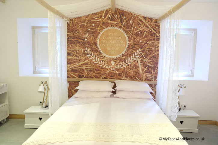 A restful bedroom in the Luz Houses. There is a message on the headboard to encourage guests to venture out of their comfort zone.