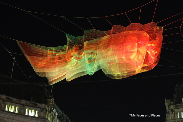 6. 1.8 London: Fabric that flows with the breeze above Oxford Circus. The breeze flowing along Oxford Street and Regent Street cause the fabric to change its shape. The colours on the material change constantly. This is a fascinating piece – changes of shape and colours with time.