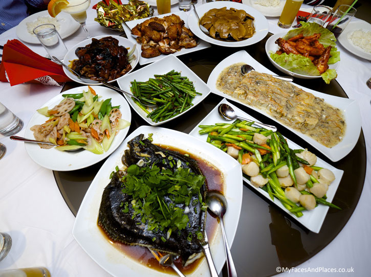 The feast of the Chinese New Year Celebrations with the Main Course of - Steamed fish, stir fried vegetables with scallops. tou foo with crab sauce, chilied king prawns, stir fried vegetables, fried chicken, braised lamb, abalone with braised chinese mushrooms.