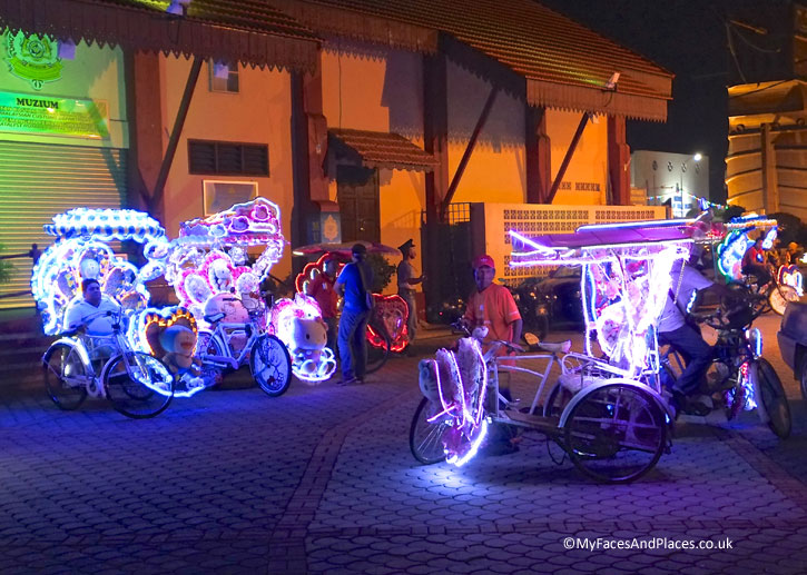 Entertainment at the Melaka River Cruise Jetty is provided by the brightly lit trishaws carrying sound systems.