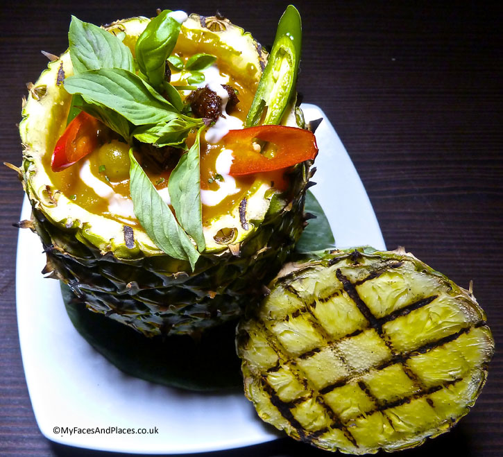 Red curry with roasted duck, grape, pineapple and cherry tomatoes served in a pineapple bowl - Ladyboys and Mango Tree Restaurant