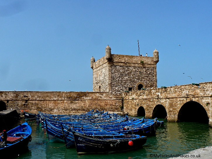 Indigo-blue fishing boats berthed by the ancient fortress