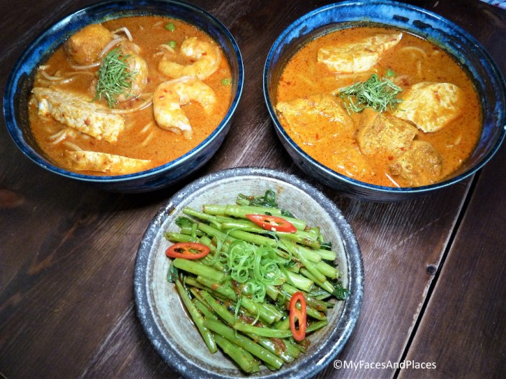 Sambal Shiok's signature dishes Chicken Laksa and Prawn & Chicken Laksa with a side dish of kangkong (water morning glory).