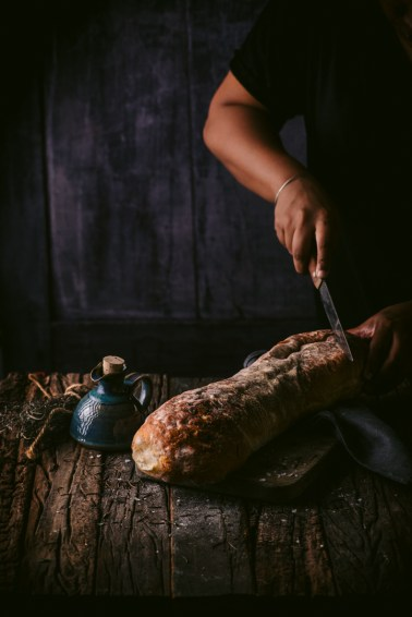 Freshly baked ciabatta being sliced in rustic barn setting with the evening sun peeking through the side window
