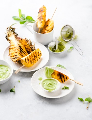 Bright & airy image of grilled pineapples on skewers dipped in vegan matcha mint choc coconut cream sauce