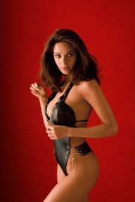 model hindi films actress Mallika Sherawat sexy photoshoot or Maxim India playing with the bikini strings standing in front of a red wall wearing string one piece leather bikini