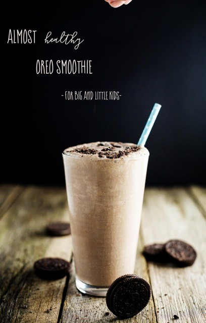 A close up of a chocolate smoothie in a tall glass with a straw with text