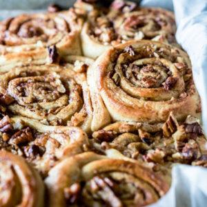 A close up of apple pecan pinwheels in a baking pan