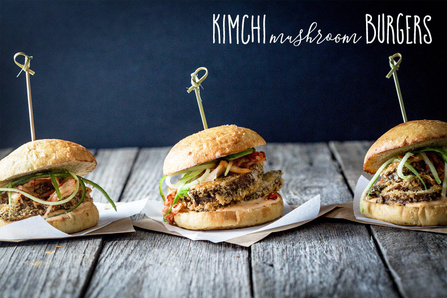 Three vegan kimchi mushroom burgers, side beside, on a rustic wooden table with a dark wall in the background.