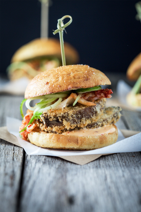 Close up image of a vegan kimchi crispy mushroom burger sitting on white baking paper on a rustic wooden table