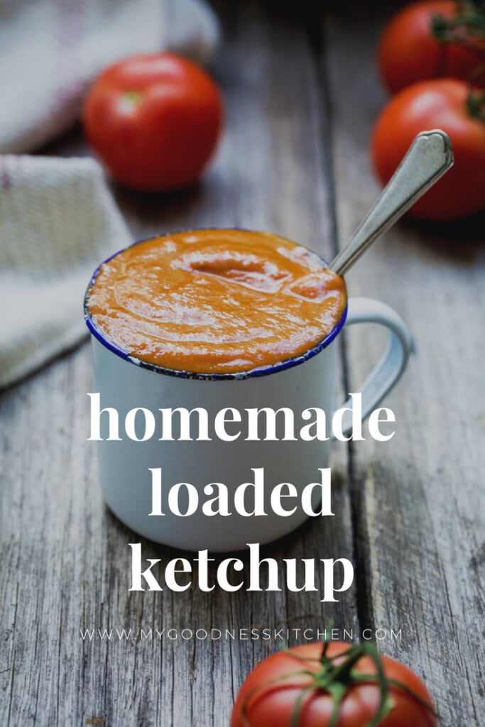 Homemade ketchup in a white metal cup with tomatoes around with text