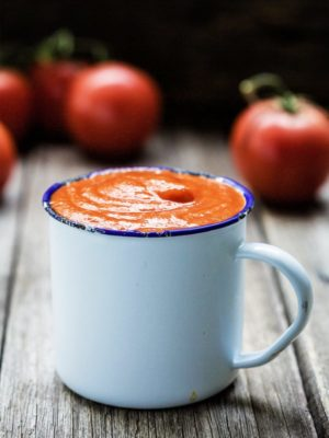 A closeup of homemade ketchup in a white metal cup with tomatoes around